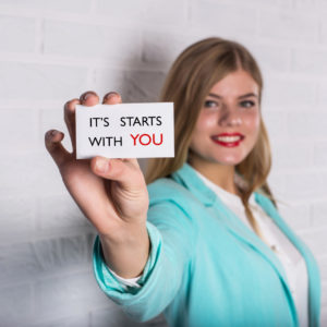 Motivational business quote. Business person in suit hold card with message. It Starts With You!
