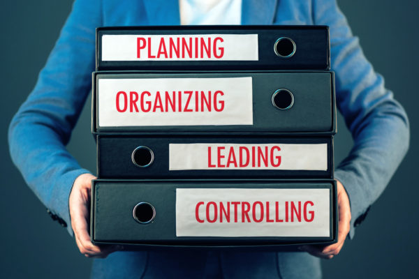 Four basic functions of management process in business organization - planning, organizing, leading and controlling.