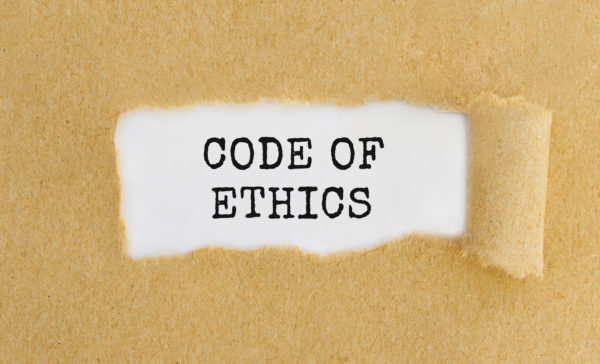 Text Code Of Ethics appearing behind ripped brown paper.