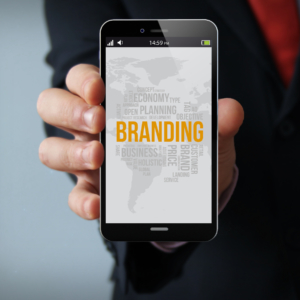 new technologies business concept: businessman hand holding a 3d generated touch phone with branding on the screen. Screen graphics are made up.